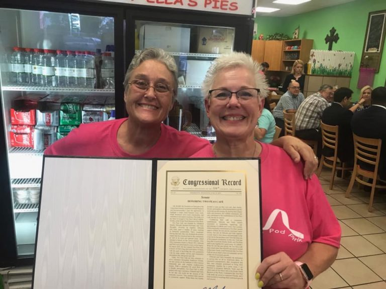 A transparency photo of the two owners of Two Peas Cafe receiving a Congressional Record