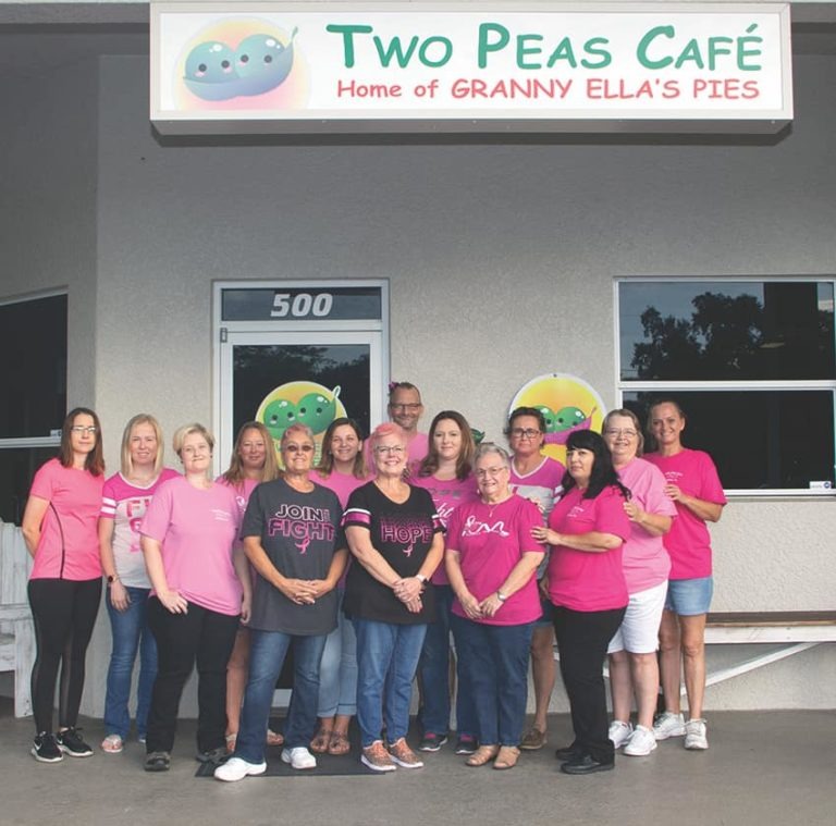 The entire Two Peas Cafe staff smiling for a picture in front of the restaurant.