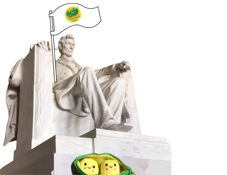 A transparency photo of a plush two peas two in front of the statue of Abraham Lincoln in the Lincoln Memorial in Washington D.C. with Lincoln holding a cartoon flag that has the Two Peas logo on it.